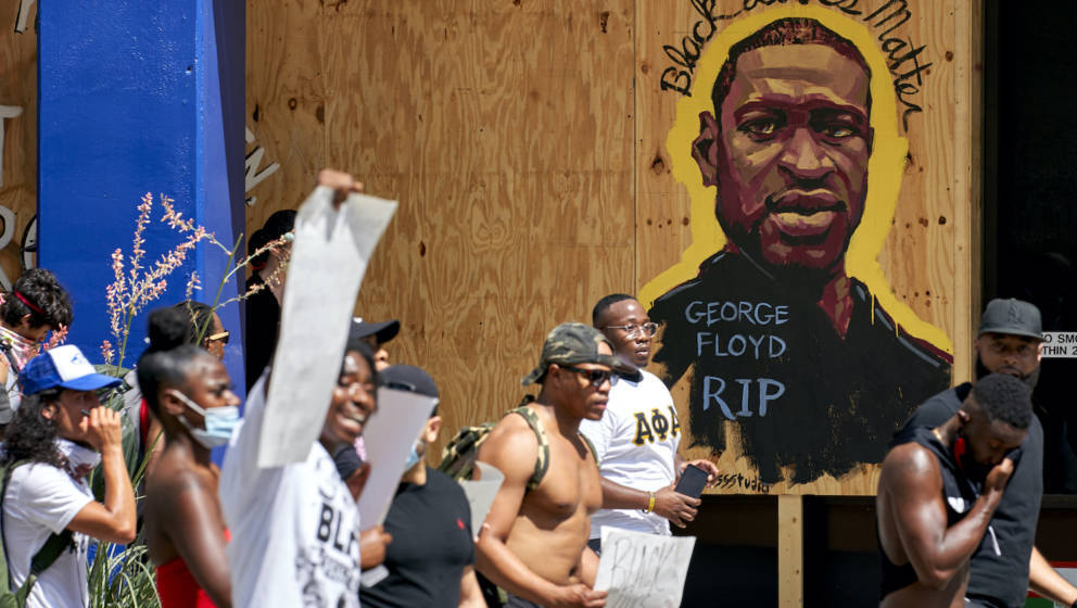 DALLAS, TX - JUNE 06: Demonstrators march past a mural remembering George Floyd during a peaceful protest against police brut
