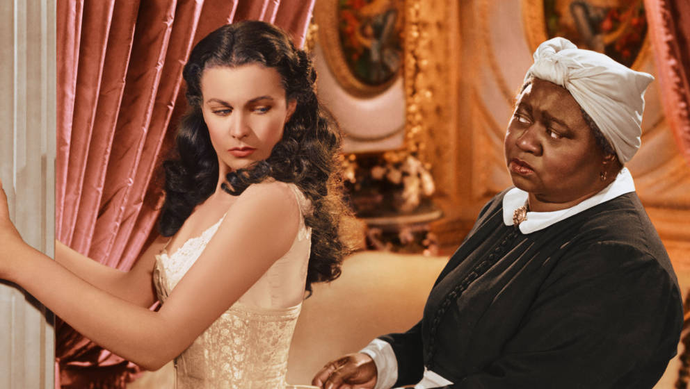 Vivien Leigh (1913-1967), British actress, has her corset tightened by Hattie McDaniel (1892–1952), US actress, in a publi