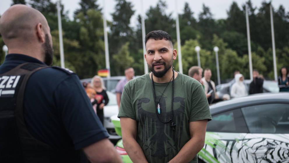 Attila Hildmann im Gespräch mit der Polizei, dahinter sein Porsche