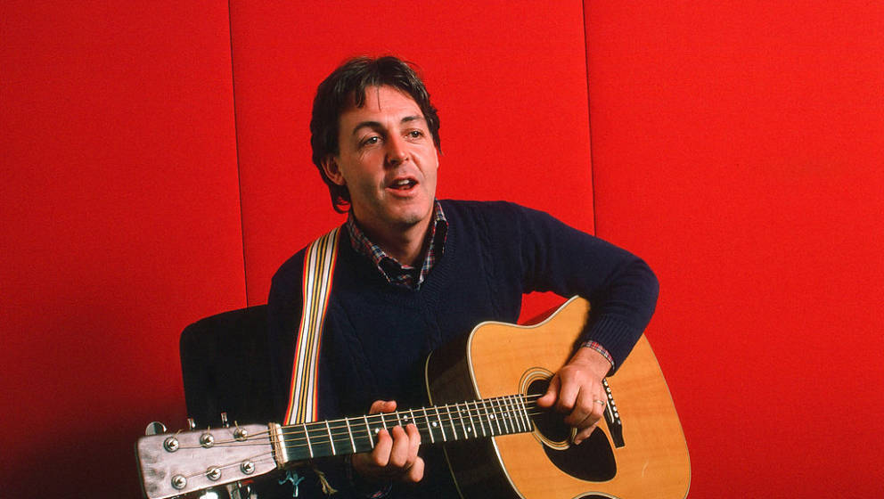 Portrait of British musician Paul McCartney as he plays acoustic guitar against a red background, October 7, 1984.  (Photo Ro