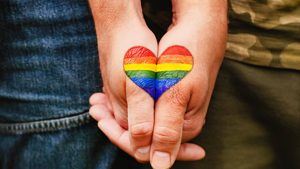 Rainbow heart drawing on hands, LGBTQ love symbol, gay couple hand in hand, homoseaxual lovers