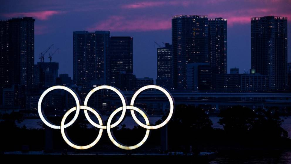 A general view shows the Olympic rings lit up at dusk on the Odaiba waterfront in Tokyo on Juky 12, 2021. (Photo by Charly TR