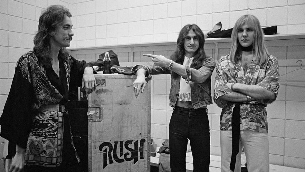 SPRINGFIELD, USA - 1st DECEMBER: Neil Peart, Geddy Lee and Alex Lifeson from Canadian group Rush pose next to a flight case b